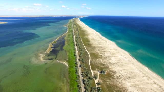 AERIAL: Sandbank between blue sea and salt lakes