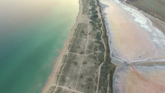 aerial: sandbar between blue sea and salt lake - backwater stock videos & royalty-free footage