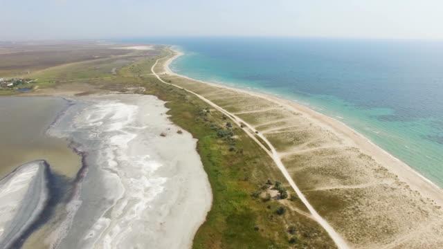 aerial: sandbar between blue sea and salt lakes - backwater stock videos & royalty-free footage
