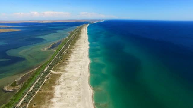 AERIAL: Sandbar between blue sea and salt lakes