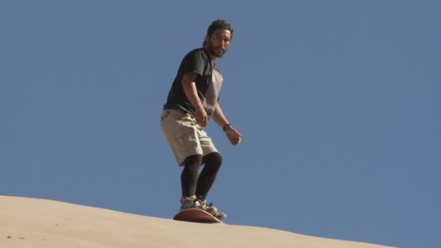 slo mo sand-boarder descends down sand dune and turns several times / san pedro de atacama, chile - solo un uomo di età media video stock e b–roll