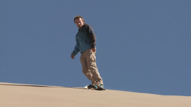 slo mo sand-boarder descends down sand dune / san pedro de atacama, chile - solo un uomo di età media video stock e b–roll
