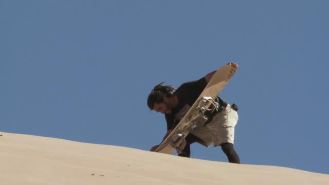 la sand-boarder prepares board on ridge of sand dune / san pedro de atacama, chile - solo un uomo di età media video stock e b–roll