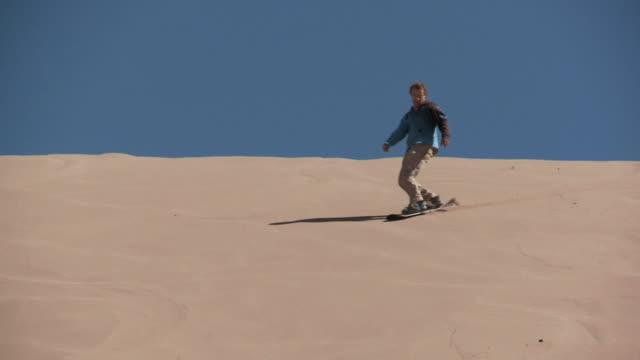 slo mo sandboarder skiing downhill on sand dune finishing with jump / san pedro de atacama, norte grande, chile - sand dune stock videos & royalty-free footage