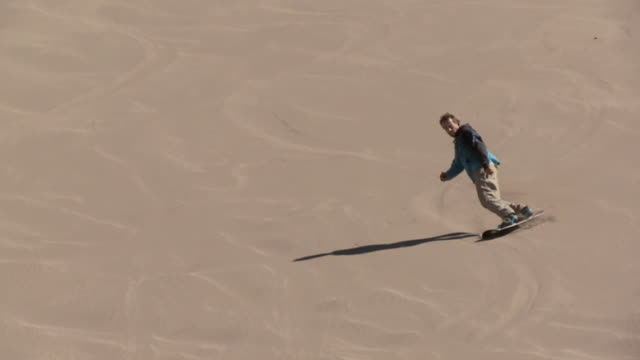 TS Sand-boarder skis down dune and jumps into the air / San Pedro de Atacama, Norte Grande, Chile