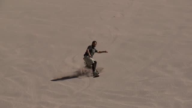 la sand-boarder skis down dune and jumps into the air / san pedro de atacama, norte grande, chile - solo un uomo di età media video stock e b–roll