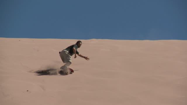 la sand-boarder skis down dune and performs jump / san pedro de atacama, norte grande, chile - solo un uomo di età media video stock e b–roll