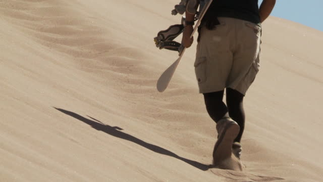 ts sand-boarder walking slowly up sand dune with board in his hand / san pedro de atacama, norte grande, chile - sand dune stock videos & royalty-free footage