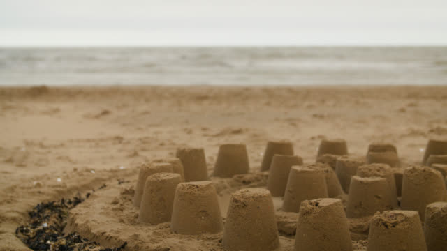 sandcastle on beach on overcast day - beige stock videos & royalty-free footage