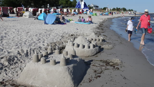 vidéos et rushes de sandcastles stand at the beach at high summer temperatures around 30 degrees celsius during the novel coronavirus crisis on august 13 2020 in... - chapeau de soleil