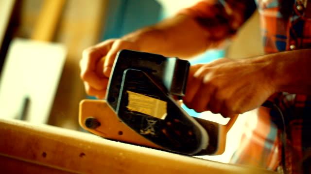 Sanding a piece of wood.