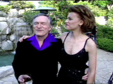 mcu sandra bernhard and hugh hefner posing for pictures together in backyard of playboy mansion waterfall in bg - playboy mansion stock videos & royalty-free footage