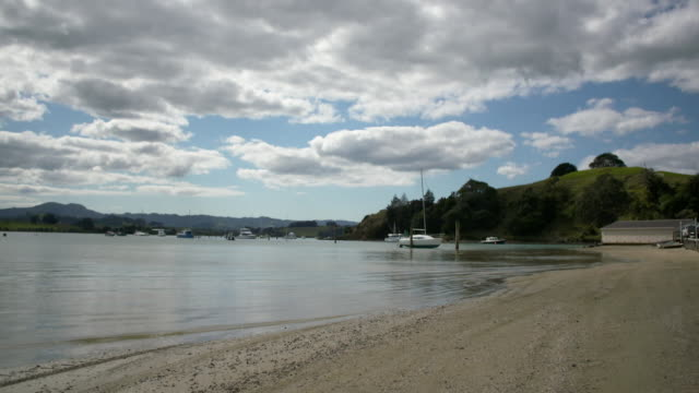sandspit beach north of auckland with boats at moorings, waves lapping at beach and ferry terminal - auckland ferry stock videos & royalty-free footage