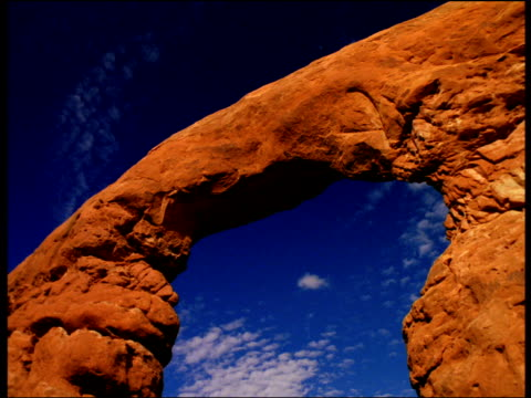 a sandstone arch frames blue sky and white clouds. - sandstone stock videos & royalty-free footage