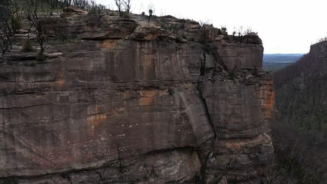 sandstone cliff, escarpment, after forest fire in valley, aerial view - ロックストラータ点の映像素材/bロール