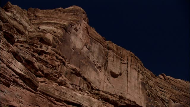 a sandstone cliff towers beneath a blue sky. - sandstone stock videos & royalty-free footage