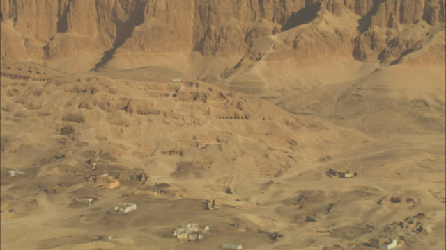 sandstone cliffs surround a town in the egyptian desert. - town stock videos & royalty-free footage