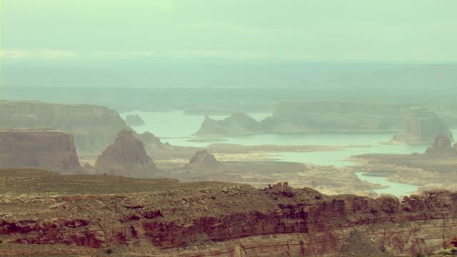 vídeos de stock e filmes b-roll de sandstone formations tower above a lake in the utah desert. - chaminé de fada