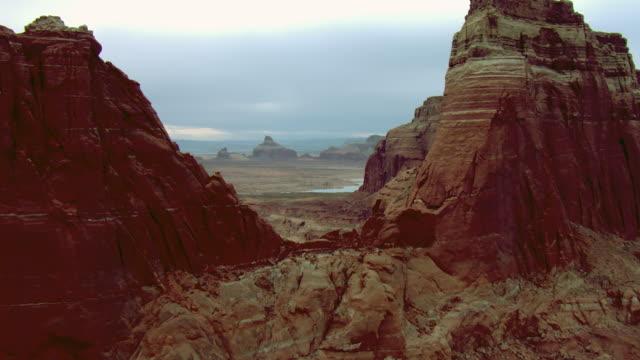 vídeos de stock e filmes b-roll de sandstone formations tower above the desert near a lake. - chaminé de fada