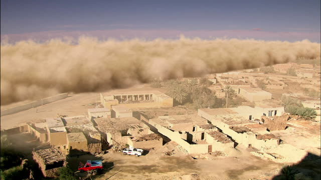 a sandstorm blows into a desert valley and covers a city. - sandstorm stock videos & royalty-free footage