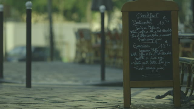 vídeos y material grabado en eventos de stock de a sandwich board containing a blackboard advertises, in english, two breakfast menus to tourists visiting paris, france. - pizarra medios visuales