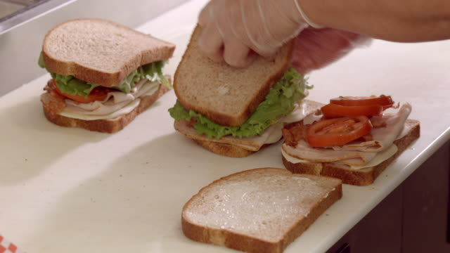 ecu sandwich shop cutting board area where hands wearing protective gloves prepare bacon lettuce and tomato sandwich  / cabazon, california, usa - making a sandwich stock videos and b-roll footage