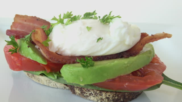 BLT Sandwich with Avocado and Poached Egg. Served Open Faced on Rustic Artisan Whole Wheat Bread