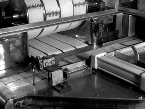 sandwiches are cut to size and wrapped in cellophane on an automated production line at a sandwich factory 1955 - cellophane stock videos & royalty-free footage