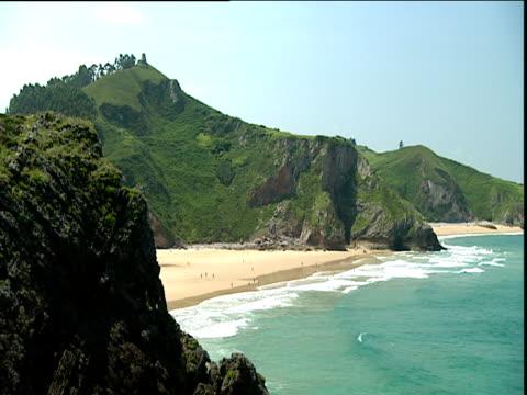 vídeos y material grabado en eventos de stock de sandy bay with waves lapping onto shore from aqua green sea large moss covered cliffs in background - musgo español