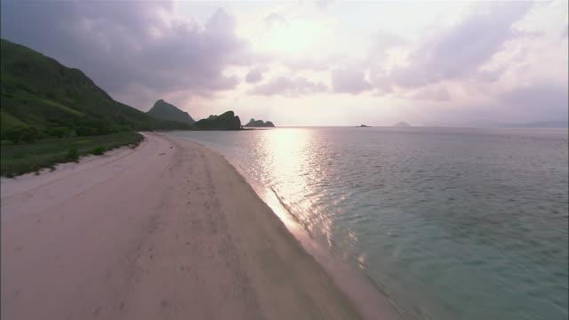 low aerial sandy beach and green hills on komodo island / komodo national park, east nusa tenggara, indonesia - seascape stock videos & royalty-free footage