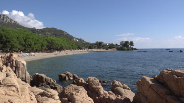 pan / sandy beach at rocky coast - spiaggia stock videos & royalty-free footage