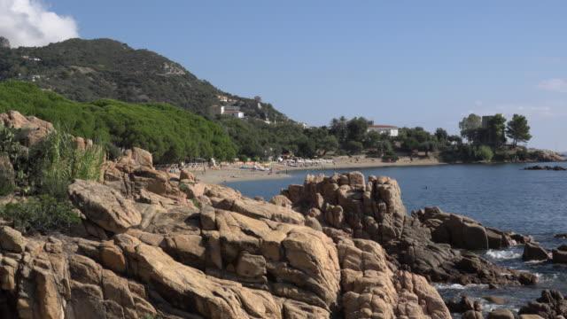 sandy beach at rocky coast - spiaggia stock videos & royalty-free footage