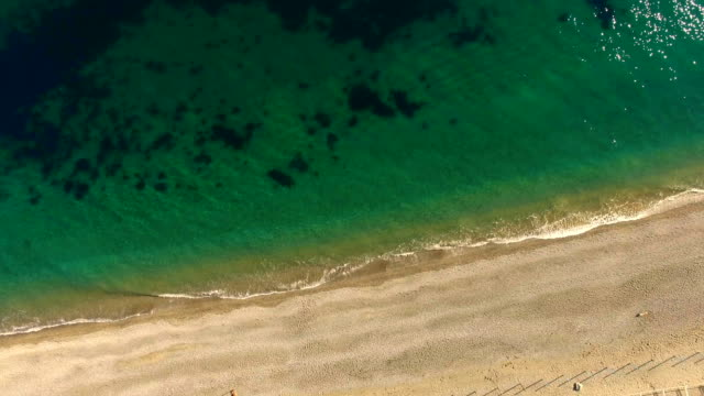 Sandy beach with clear sea water, aerial video