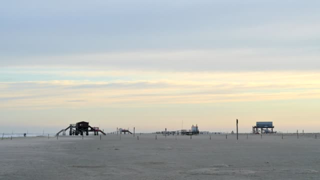 sandy beach with stilt houses at sunrise, norderdeich, sankt peter-ording, north friesland, north sea, schleswig-holstein, germany - schleswig holstein stock videos & royalty-free footage