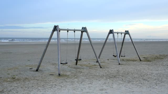 sandy beach with swing at sunrise, norderdeich, sankt peter-ording, north friesland, north sea, schleswig-holstein, germany - schleswig holstein stock videos & royalty-free footage