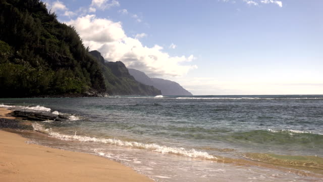 sandy beach with waves on coast of kauai island - butte rocky outcrop stock videos & royalty-free footage