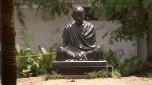 sandy ground and vegetation surround a statue of gandhi at the gandhi ashram. available in hd. - mahatma gandhi stock videos & royalty-free footage