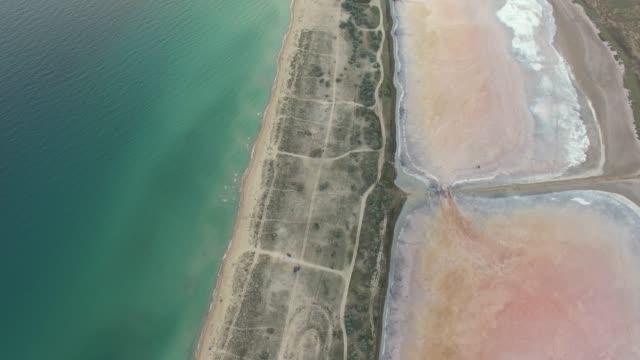 航空写真: 青い海と塩の湖の間の浅い水の土地のサンディ - 逆水点の映像素材/bロール