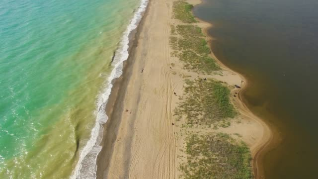 aerial: sandy land in shallow water between blue sea and salt lake - rock type stock videos and b-roll footage