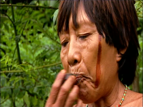 Sanema tribes woman chews tobacco and spits saliva from mouth South Venezuelan Rainforest