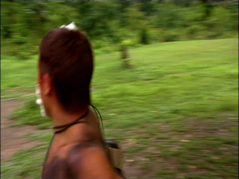 sanema tribesman runs towards village huts and dances under influence of sakona hallucinogen south venezuelan rainforest - tetto di paglia video stock e b–roll