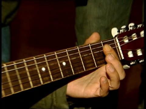 1200 asylum seekers allowed to enter Britain Iraqi Kurd refugee playing guitar as others listen