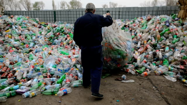 sanitary worker in a recycling center.working at a recycling factory - gettata video stock e b–roll