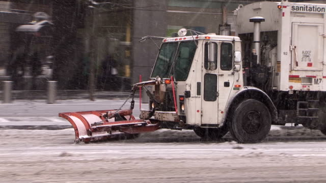 Sanitation trucks plow snow from roads