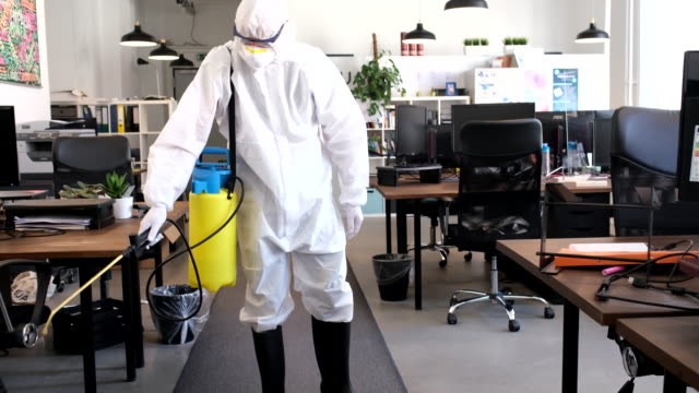 sanitation worker in ppe suit disinfecting office area - rubbing alcohol stock videos & royalty-free footage