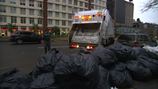 a sanitation worker on a street helps a garbage truck driver reverse toward garbage bags. - bin bag stock videos & royalty-free footage
