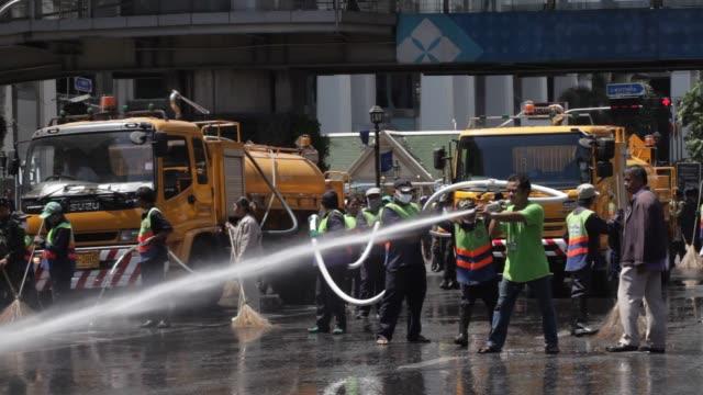 Sanitation workers clean the sidewalks at the blast site near the Erawan Hindu shrine in Bangkok Thailand on August 17th 2015 Shots Sanitation trucks...