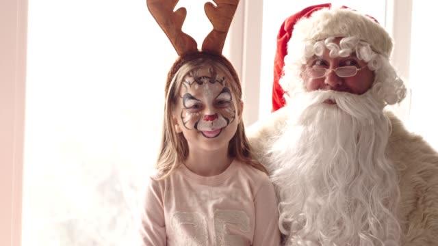Santa and girl wearing reindeer antler headband