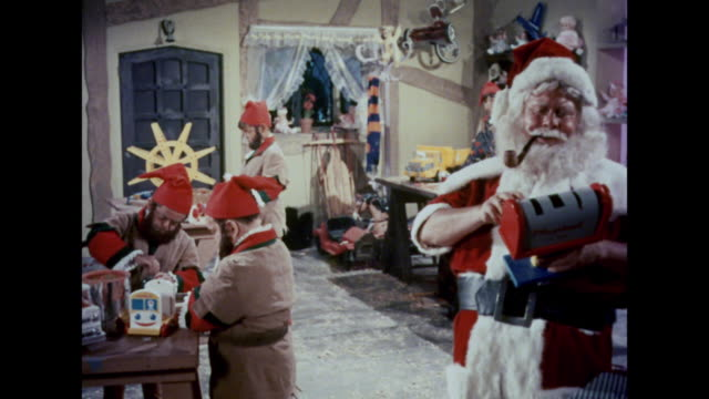 vídeos de stock e filmes b-roll de 1964 santa and his elves build toys in his workshop - pai natal