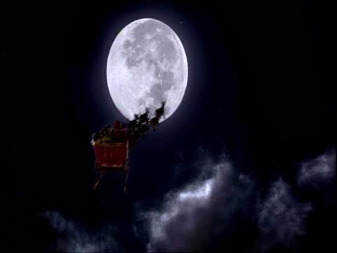 santa and his reindeer fly toward the moon. - weihnachtsmann schlitten stock-videos und b-roll-filmmaterial